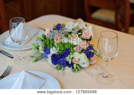 beautiful wedding boquet lying on table in restaurant.