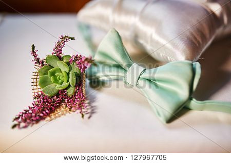 Close-up butterfly of groom and boutonniere on table.