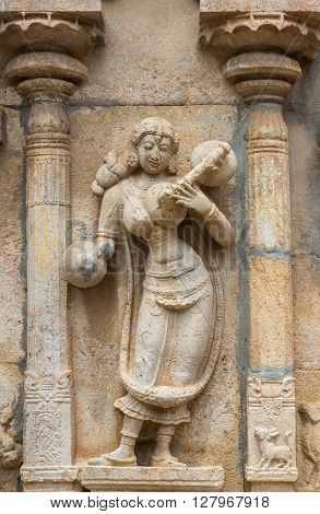 Trichy India - October 15 2013: Sandstone statue of musical woman with instruments at Ranganathar Temple. Outside wall of old part built during Madurai Nayak era. Traditional dress.