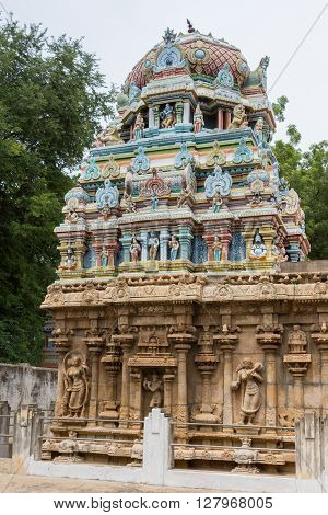 Trichy India - October 15 2013: Colorful short Vimanam on top of older temple building at Ranganathar Temple built during Madurai Nayak era. Statues on wall of sandstone base.