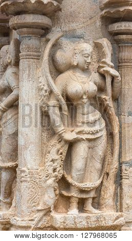 Trichy India - October 15 2013: Sandstone statue of dancing woman at Ranganathar Temple. Outside wall of old part built during Madurai Nayak era. Traditional dress and admiring parrot.
