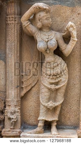Trichy India - October 15 2013: Sandstone statue of woman looking at herself in handheld mirror at Ranganathar Temple. Outside wall of old part built during Madurai Nayak era.