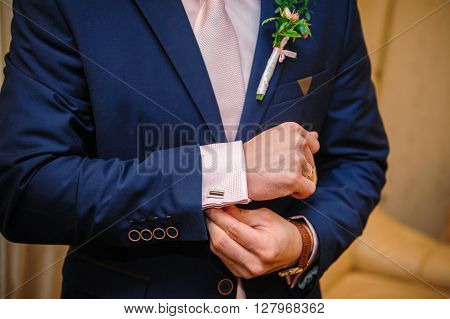 groom in a suit hands wear cufflinks in room.