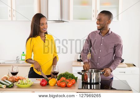 Young African Couple Cooking Food At Kitchen