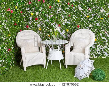 White wicker rattan furniture in the blooming garden. Vintage tracery umbrella