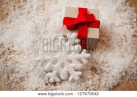 Christmas gift kraft paper and a snowflake in the snow.