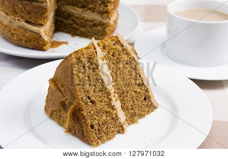 Coffee and walnut cake served with a cup of tea A traditional coffee and walnut cake covered with butter cream