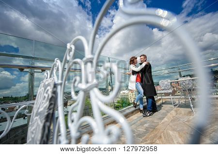Couple happy in love hugging near railing Fashion lifestyle photo.