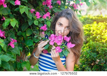 portrait of young beautiful woman on background of bougainvillea purple violet flowers in blossom.
