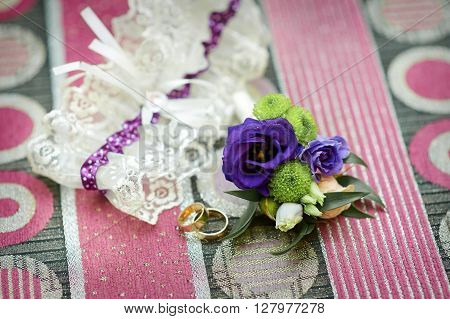 Wedding accessories bride's garter, rings and boutonniere.