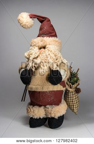 Santa Claus doll wearing a sweater. In the hands of ski poles and bag with gifts. The bag is visible spruce branch. Doll is looking to the left.