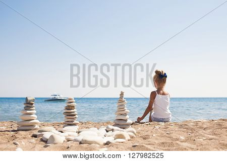 Beautiful sea shore landscape with girl sitting in front of the sea on the sand