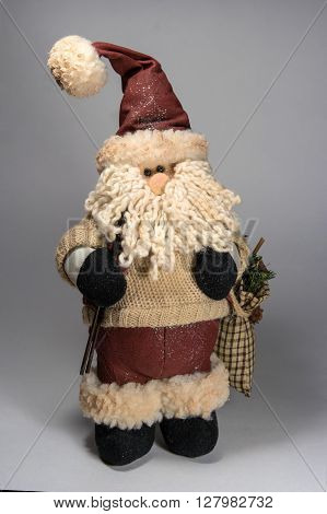 Santa Claus doll wearing a sweater. In the hands of ski poles and bag with gifts. The bag is visible spruce branch. Doll looks right.