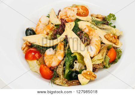 Fresh mixed green salad with shrimps cherry tomatoes and olives isolated on white bachground