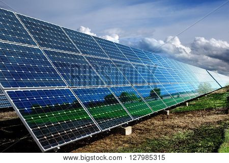 Row of photovoltaic solar panels and dramatic sky background