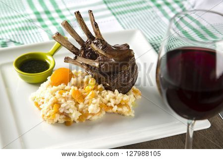 A Delicious Dish Of Rack Of Lamb With Rice And Apricot On A Square Plate.