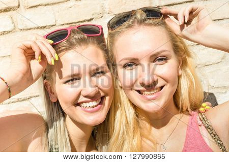 Young fashion women girls taking selfie against stonewall - Summer concept with happy girlfriends having fun together - Best female friends with sunglasses catching moment - Warm afternoon color tone