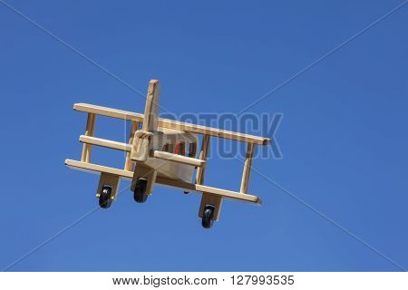 Wooden Plane flying with blue sky - Going away