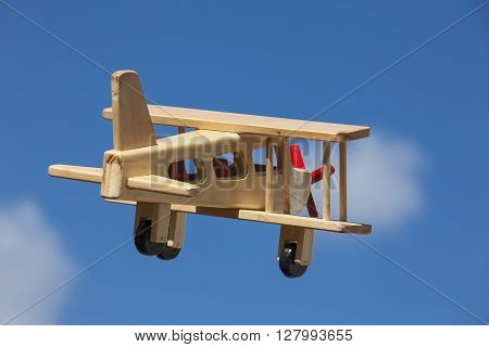 Wooden Plane flying with blue sky and white clouds - Going away