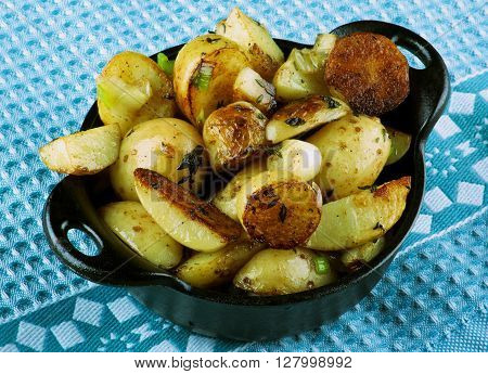Homemade Roasted Potato Wedges and Halves with Onion and Greens in Black Cast Iron Pot closeup on Blue Napkin