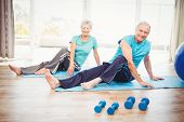 Portrait of smiling senior couple performing yoga at home poster