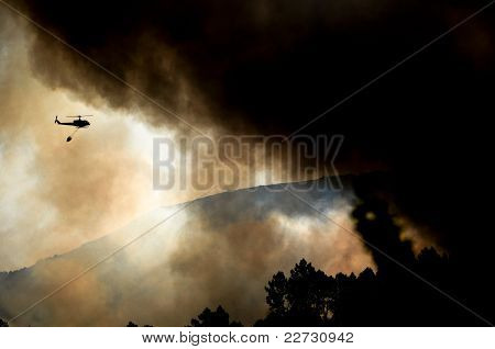 helicopter flying over forest fire