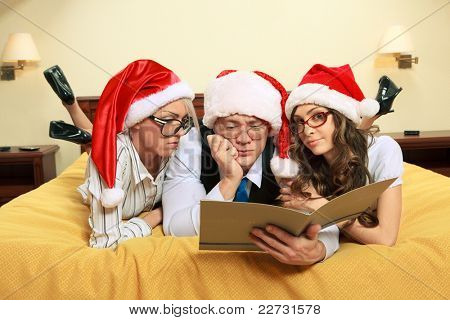 Manager with two his subordinates reading a business plan on New Year's night