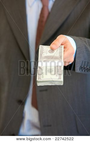 Businessman Giving Stack Of Dollars. Close-up.