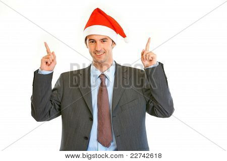 Smiling Young Businessman In Santa Hat Pointing Finger Up At Copy Space