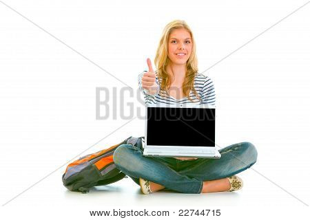 Smiling Pretty Girl Sitting On Floor With Laptop And Showing Thumbs Up