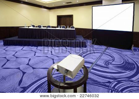 Big table with microphone near screen in bright conference hall, view from projector