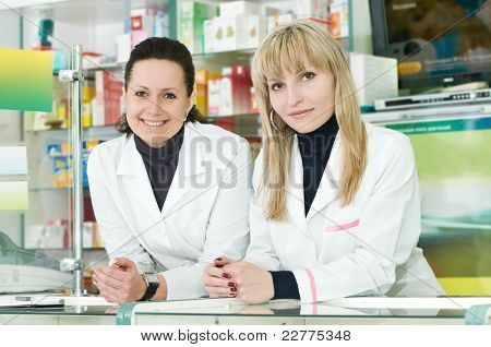 Two Happy cheerful pharmacist chemist women standing in pharmacy drugstore