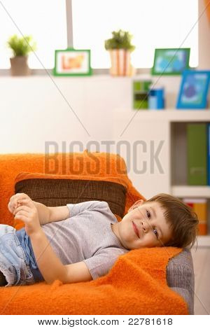 Portrait of young boy lying on sofa at home, looking at camera, smiling.?