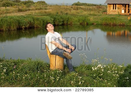 Happy Man Relaxes On The Lakeside