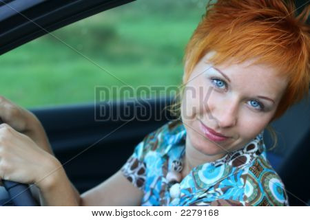 Young Red-Haired Woman Is Siting In A Car. Woman Is Happy