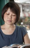 picture of asian woman  - Middle aged Asian woman relaxing with a drink - JPG