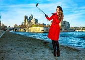 Bright In Paris. Happy Young Traveller Woman In Red Trench Coat On Embankment Near Notre Dame De Par poster