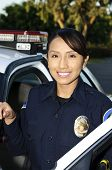 stock photo of lightbar  - a Hispanic female police officer smiling next to her patrol car - JPG