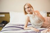 Happy Businesswoman At The Hotel Room, Lying On The Bed And Talking On Phone. Business Lady Went To  poster