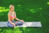 Young Woman Outdoors, Meditation Exercises. Girl Does Lotus Pose For Relaxation. Wellness, Calmness, poster