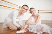 Ballet teacher helping her little learner to tie ribbons of pointe before class poster