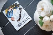 Popular Journal. Close-up Top View Of Black Coffee Table With Glasses, Business Magazine And Vase Wi poster