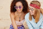 Top View Of Two Female Lesbians Embrace At Sandy Beach, Wear Sunglasses, Have Pleasant Conversation, poster