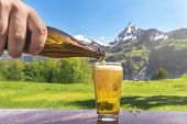Glass Of Beer And Summer Alpine Landscape - Hand Of A Man Pouring Beer From A Bottle In A Glass With poster