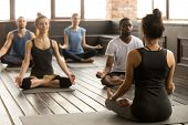 Group Of Young Sporty People Practicing Yoga Lesson With Instructor, Sitting In Sukhasana Exercise,  poster