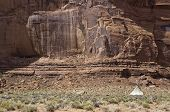 Постер, плакат: Native Indians Tent In Front Of A Red Rock Cliff In A Remote Spot In The Famous Monument Valley Usa