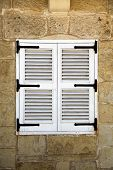 stock photo of louvers  - A little louvered white window on a limestone facade - JPG
