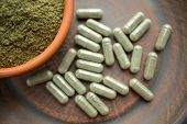 Supplement Kratom Green Capsules And Powder On Brown Plate. Herbal Product Alt-medicine Kratom Is  O poster