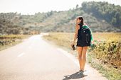 Young Backpacking Adventurous Woman Hitchhiking On The Road.traveling Backpacks Volume,packing Essen poster