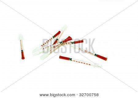 bunch of red syringes placed over a white background